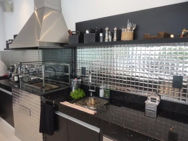 Cozinha gourmet com pastilhas de inox espelhadas entre a bancada e a prateleira de utensílios. Fonte.